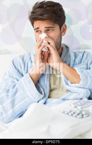 Homme malade soufflant son nez dans du papier de soie sur le lit chez lui
