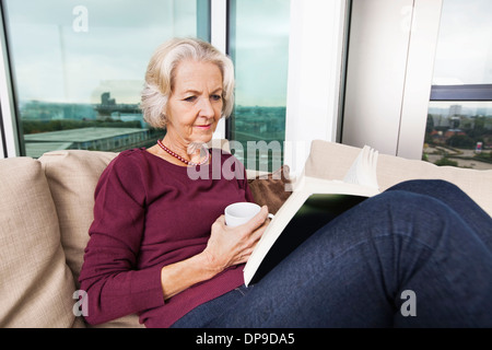 Senior woman reading book on sofa at home Banque D'Images