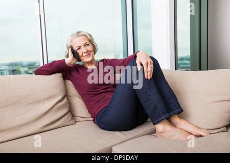Full-length of senior woman répondre à smart phone on sofa at home Banque D'Images