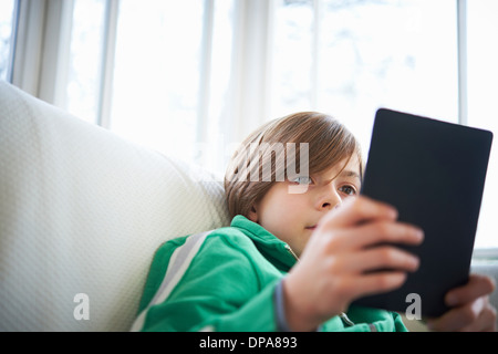 Boy on sofa using digital tablet Banque D'Images
