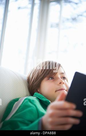 Boy on sofa using digital tablet Banque D'Images