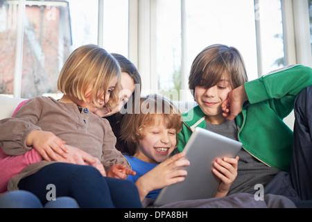 Frères et sœurs using digital tablet together Banque D'Images
