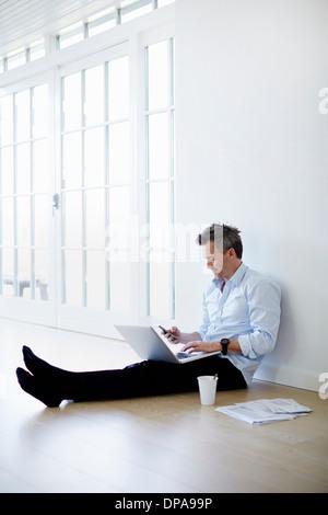 Homme assis sur le plancher à l'aide d'ordinateur portable et téléphone