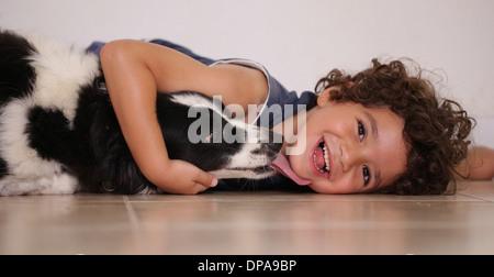 Young boy lying on floor serrant son chien de compagnie Banque D'Images