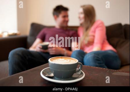 Jeune couple se prélasser sur un canapé dans la salle de cafe Banque D'Images