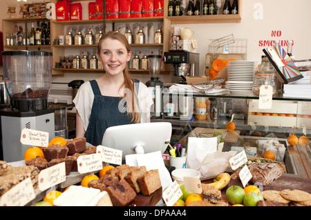 Jeune femme derrière la cuisine in cafe Banque D'Images