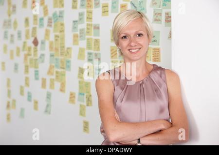 Portrait of mid adult woman with adhesive notes en arrière-plan Banque D'Images