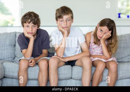 Frères et sœur sur canapé à ennuyer Banque D'Images