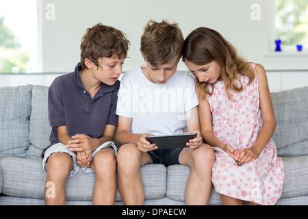 Frères et sœur on sofa looking at digital tablet Banque D'Images