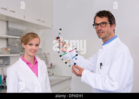 Portrait de deux scientifiques avec le modèle moléculaire de l'adn