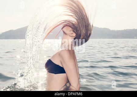 Jeune femme en jetant la tête en arrière de la mer Banque D'Images