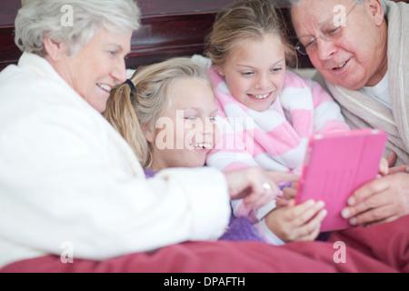 Les grands-parents et petits-enfants de jouer jeu numérique au lit