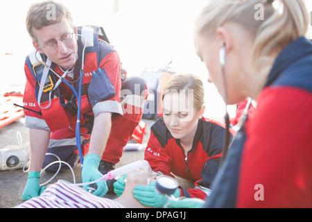 Groupe d'ambulanciers paramédicaux ayant tendance patient sur road Banque D'Images