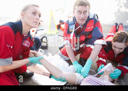 Trois ambulanciers tendant patient lying on road Banque D'Images