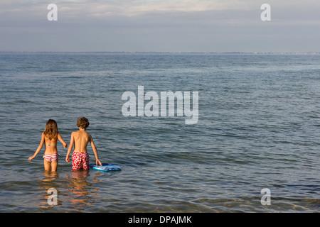 Frère et sœur paddling in sea Banque D'Images
