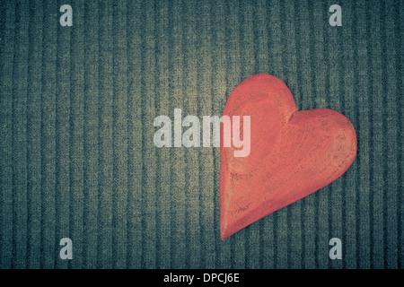 Coeur en bois rouge sur fond tricoté. Copier l'espace. Image aux tons Vintage Banque D'Images