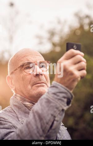 Senior man using cellular phone Banque D'Images
