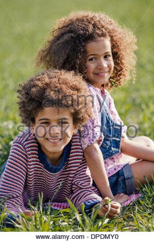 Portrait de frère et sœur lying on grass in sunlight Banque D'Images