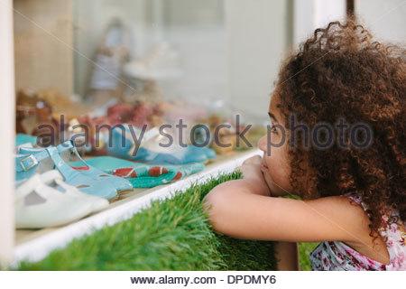 Jeune fille à la fenêtre du magasin de chaussures par Banque D'Images