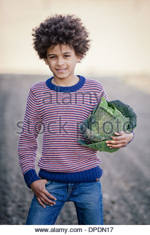 Portrait of boy in field holding cabbage Banque D'Images