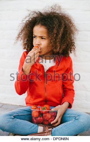 Young Girl sitting cross legged eating strawberries Banque D'Images
