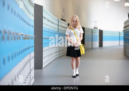 Lycéenne malheureux de marcher seul dans les couloir d'école Banque D'Images
