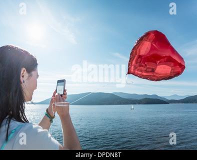 Young woman photographing ballon en forme de coeur Banque D'Images