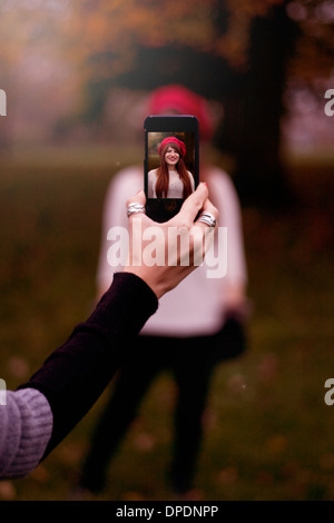Hand holding smartphone, taking photograph of young woman Banque D'Images