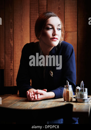 Young woman sitting in cafe with hands clasped