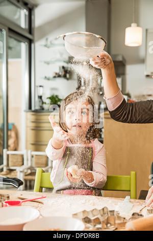 Mère et fille de tamisage de la farine en cuisine Banque D'Images