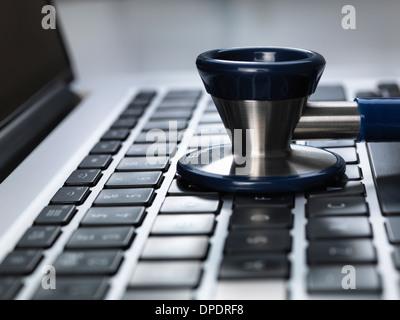 Stéthoscope assis sur un coffre illustrant en ligne santé et bureau du médecin Banque D'Images