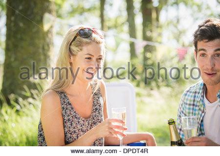 Jeune couple avec champagne en forêt Banque D'Images