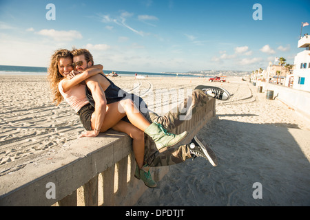 Young couple sitting on wall at San Diego beach Banque D'Images