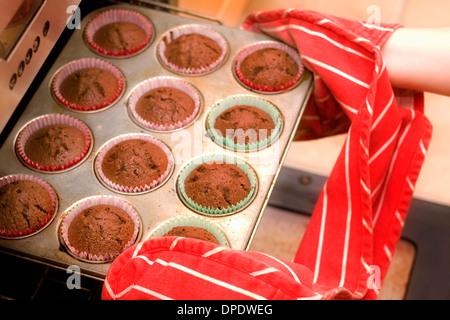 Retrait de cupcakes du four Banque D'Images