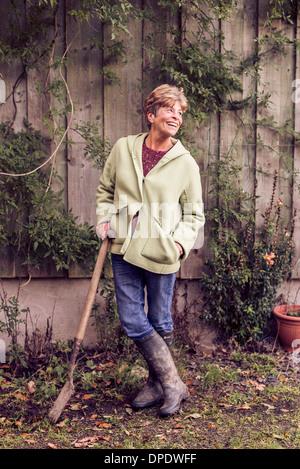 Portrait of mature woman leaning on chat dans jardin Banque D'Images