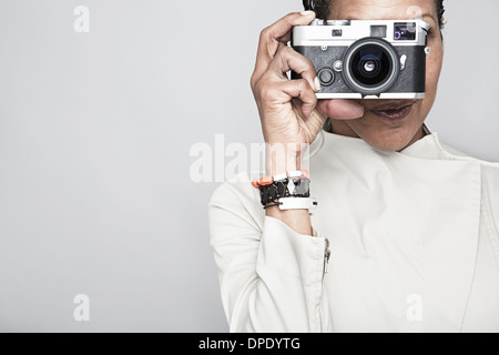 Studio portrait of young woman holding up camera Banque D'Images