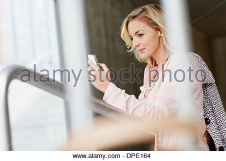 Businesswoman using mobile phone in office building Banque D'Images