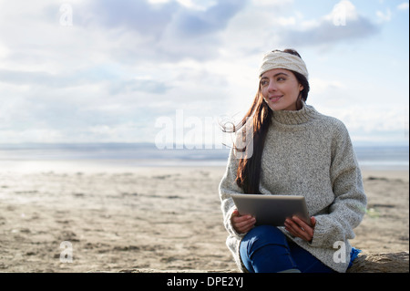 Young woman using digital tablet, Brean Sands, Somerset, Angleterre Banque D'Images