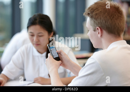 Teenage boy using cell phone in classroom Banque D'Images