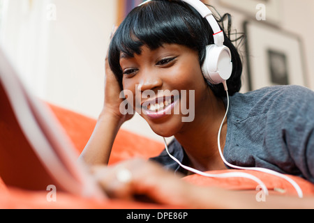 Young woman lying on sofa using digital tablet Banque D'Images
