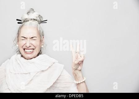 Studio portrait of senior woman sophistiquées faisant signe de victoire Banque D'Images