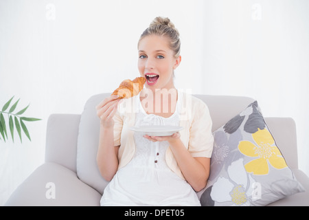 Smiling model eating croissant frais sitting on sofa Banque D'Images