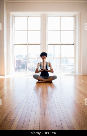 Woman practicing yoga in room Banque D'Images