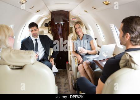 Les gens d'affaires ayant des boissons sur Jet Privé Banque D'Images