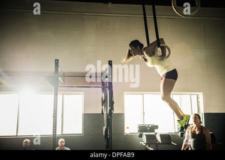 Jeune femme sur les anneaux de gym surveillée par formateur Banque D'Images