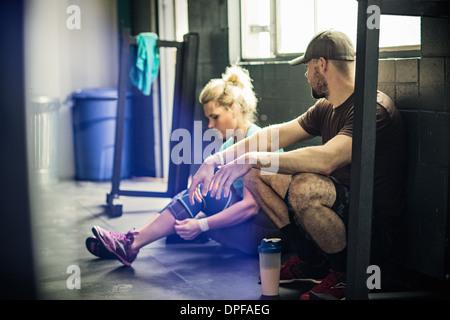 Jeune femme parlant à Trainer in gymnasium Banque D'Images