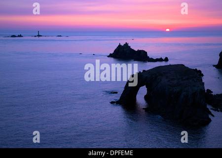 Coucher de soleil au phare, Dodnan Enys drakkars et le chevalier armé, Lands End, Cornwall, Angleterre, Royaume Banque D'Images