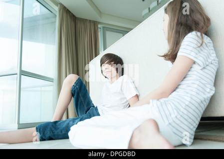 Frère et soeur assis sur le sol, appuyé contre le dos de canapé Banque D'Images