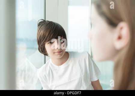 Teenage boy leaning against window Banque D'Images