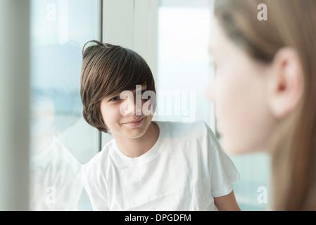 Teenage boy leaning against window, smiling at girl en premier plan Banque D'Images